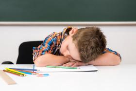 übermüdeter junge in der schule